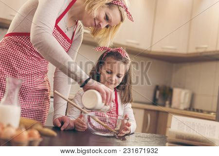 Mother And Daughter Baking Dough In The Kitchen. Mother Adding Flour From A Jar Into A Bowl