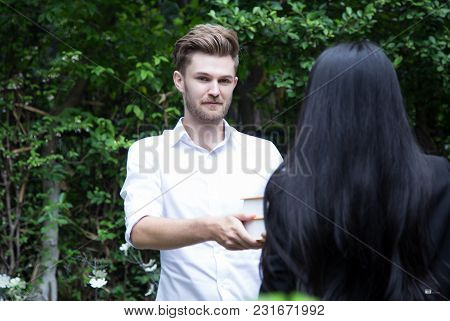 Handsome Young Man Offers A Book To His Friend In Garden