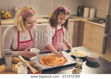 Mother And Daughter In The Kitchen Making Pizza, Daughter Spreading Ketchup On Pizza Dough With Kitc