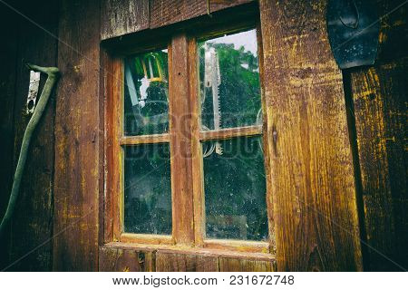 Dirty And Dusty Window On An Old Wooden Barn, With Working Tools Behind The Glass. Close Up Of Old W