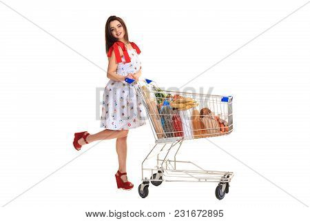 Young Woman With Full Shopping Cart On White Background. Brunette In A Summer Dress Makes Purchases,