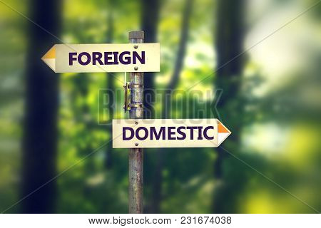 Signpost In A Park With Arrows Pointing In Two Opposite Directions Foreign And Domestic