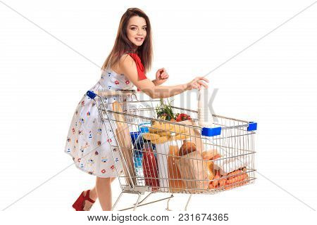 Smiling Young Woman Doing Grocery Shopping At The Supermarket, She Is Putting A Milk Bottle In The C