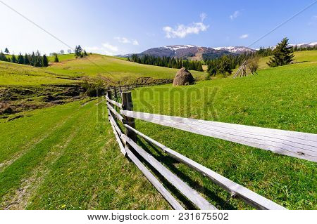 Haystack Behind The Wooden Fence On A Grassy Hill. Beautiful Carpathian Countryside In Springtime. M