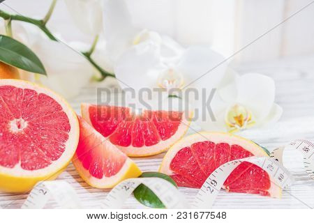 Fresh Red Grapefruit And Grapefruit Slices And Measuring Tape, On Rustic White Wooden Table Opposite