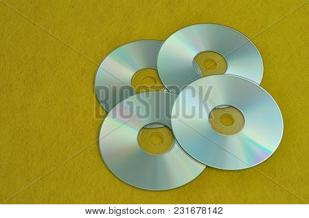 Four Cd's On A Yellow Background