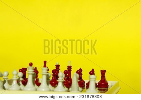 Chess Figures Over Yellow Background With A Lot Of Copy Space For Text. Abstract Colored Background