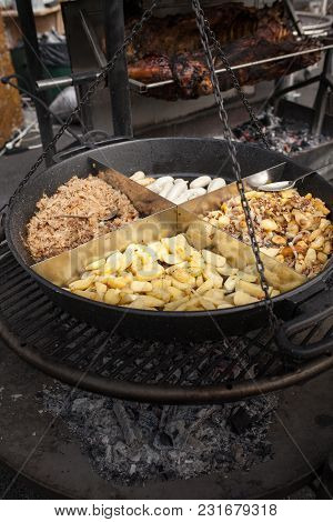 Roasted Potatoes Cooked Outdoors In Big Metal Cauldron Pot. Street Fast Food
