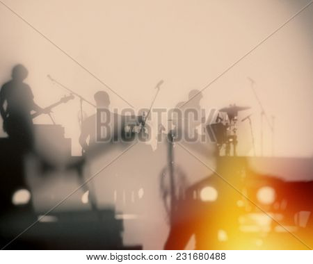 Concert Of A Musical Rock Band. Silhouettes Of Musicians On A Set Background. Blurred Background.