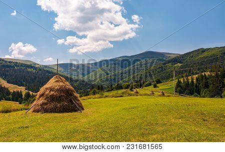 Beautiful Rural Scenery In Mountains. Haystacks On A Grassy Hillside Near The Forest On A Rolling Hi