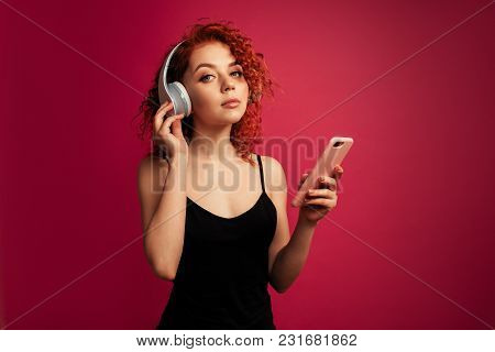 Beautiful Redhead Girl In Big White Headphones With Phone In Hand Listening To Music In The Studio O
