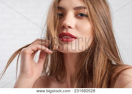 Beautiful Caucasian Model Wearing Eye Make Up And Red Lipstick Playfully Looking To Camera With Half
