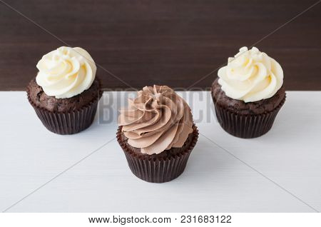 Cupcakes With Whipped Chocolate And Vanila Cream, On Black And White Wooden Table. Picture For A Men
