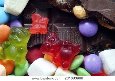Macro Detail Of Gummy Bears, Chocolate And Sour Candy On Colored Smarties Background