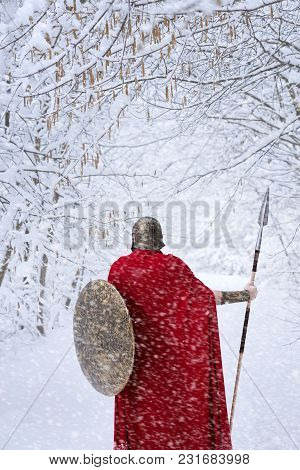 Spartan Warrior Walks In Snowy Winter Forest In Traditional Long Red Cape. He Keeps A Sharp Spear An