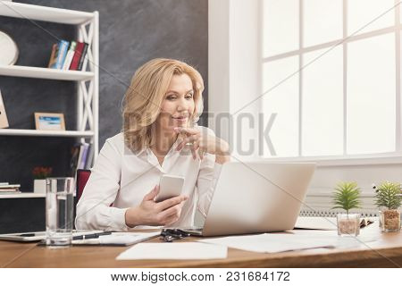 Businesswoman Working On Laptop At Office, Typing Something On Computer And Holding Smartphone While