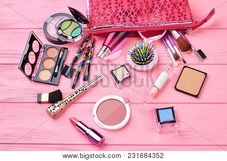Various Makeup Products On Wooden Background. Decorative Cosmetics Variety On Pink Wooden Background