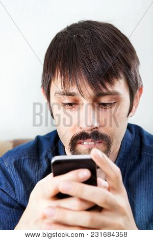 Man With Cellphone On The Sofa At The Home