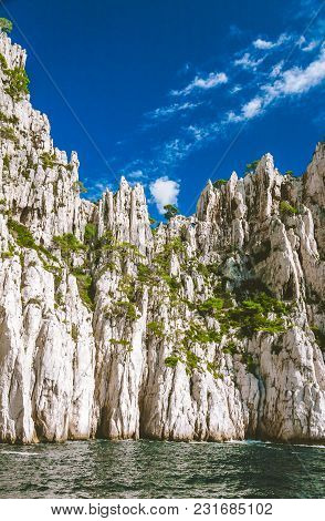High White Cliffs Of Massif Des Calanques Covered With Pine Trees Against Blue Sky In Cassis, France