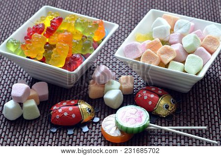 Two Ceramic Bowls Of Colored Smarties, Sour Candies, Chocolate Ladybug And Gummy Bears On Bamboo Woo
