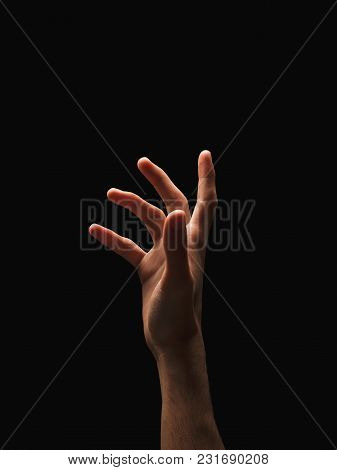 Outstretched Male Hand, Man Reaching Something Isolated On Studio Black Background - Concept Of Char
