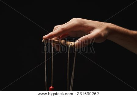 Male Hand With Marionette Strings On Black Isolated Backgorund. Manipulation, Control And Dictatorsh