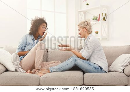 Two Multiethnic Female Friends Talking In Living Room At Home, Chatting About Their Life And Relatio