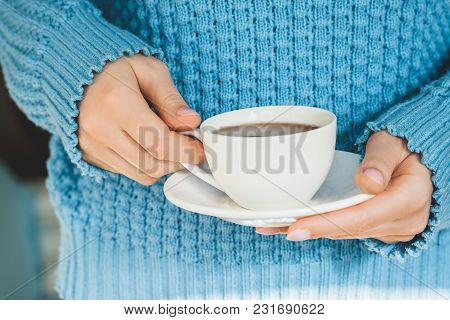 Woman Hands In A Blue Warm Knitted Sweater Holds A White Cup Of Cocoa With A Saucer.