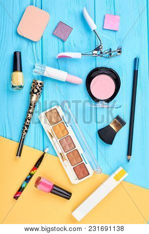 Makeup Cosmetics Set, Top View. Decorative Cosmetics Products And Makeup Tools On Blue And Yellow Ba