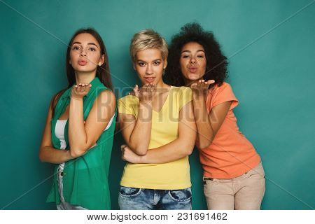Happy Female Friends Having Fun At Blue Background. Three Young Women Blowing A Kiss, Slumber Party,