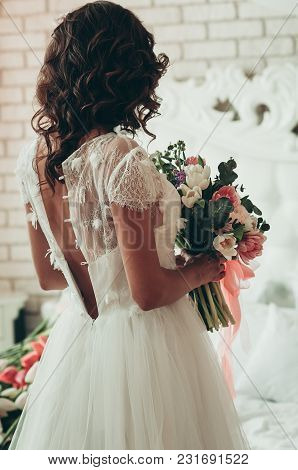 A Long Haired Brunette Bride In Unbuttoned White Dress With Wedding Bouquet, A View From The Back
