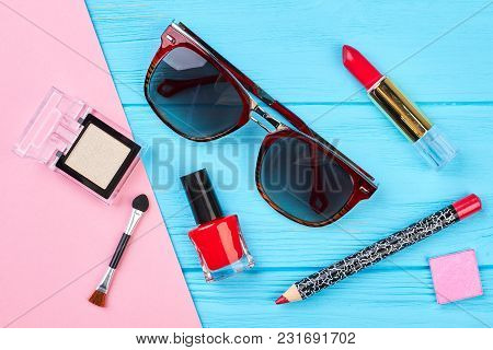 Decorative Cosmetics Set And Sunglasses. Red Makeup Objects And Stylish Sunglasses On Color Backgrou