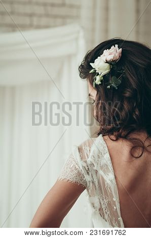 A Long Haired Brunette Bride In Unbuttoned White Dress Showing Her Back, A Closeup View