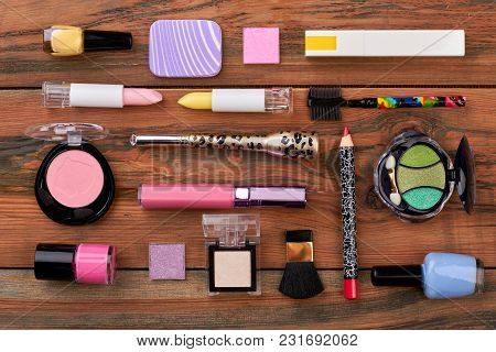 Flat Lay Cosmetics On Brown Background. Fashion Bright Cosmetics And Makeup Tools On Wooden Backgrou