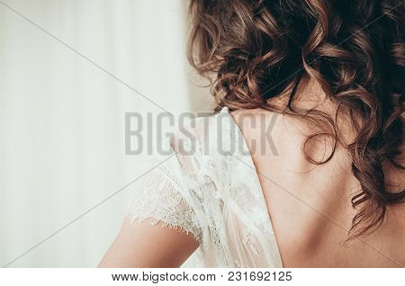A Long Haired Brunette Bride In Unbuttoned White Dress, A Closeup View From The Back