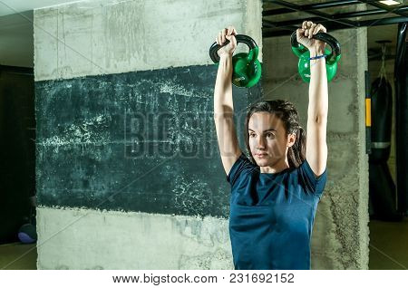 Pretty And Handsome Young Girl Holding Two Kettle Bells In Her Hands For Strength And Conditioning F