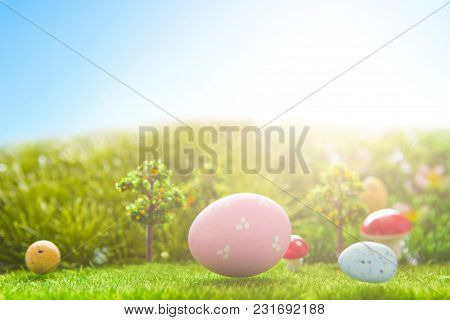 Colorful Easter Eggs And One Big Pink Easter Egg On Spring Green Grass.