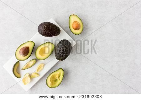 Whole, Cut And Halved Avocados On A Marble Chopping Board And Textured Gray Background. Top View.