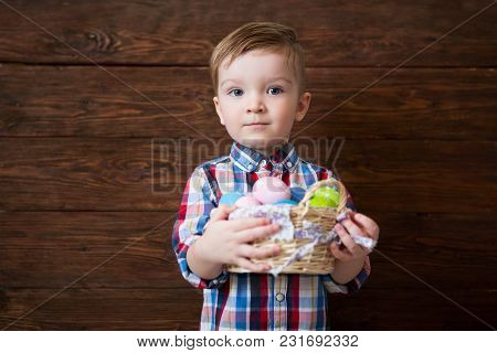Baby Boy With Easter Eggs On Basket Over Wooden Background.