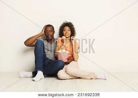 Afraid African-american Couple Watching Scary Movie At Home And Eating Popcorn, Sitting On Floor At