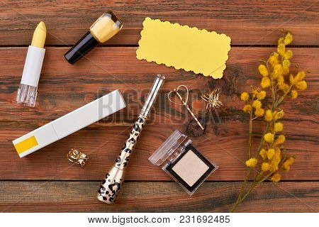 Cosmetics And Spring Plant Composition. Feminine Cosmetics Make Up Wooden Background With Yellow Pus