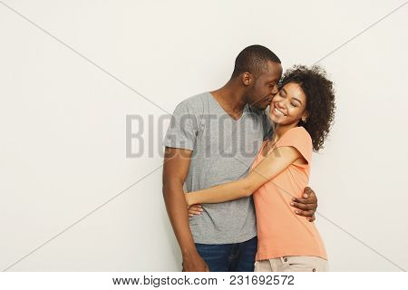 Happy African-american Couple In Casual Embracing And Smiling At White Studio Background, Love Story