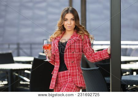 Young fashion woman with glass of wine at sidewalk cafe. Stylish female model in red tweed jacket and shorts suit