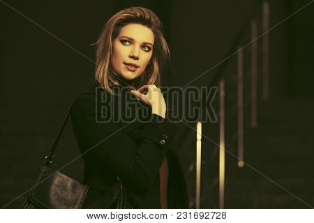 Fashion blond business woman walking in city street Stylish female model in classic black coat with handbag
