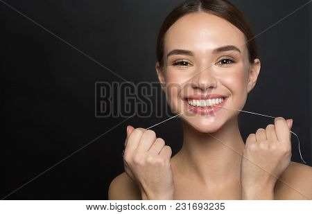 Portrait Of Positive Young Woman Who Is Taking Care Of Her Teeth. She Is Holding Dental Floss And La