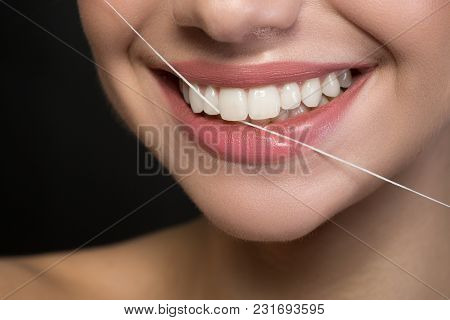 Oral Hygiene. Close Up Of Mouth Of Young Positive Woman Is Holding Dental Floss For Cleaning Teeth.