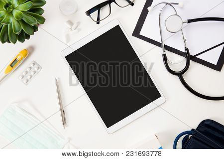 Directly Above Shot Of Tablet Computer With Pen And Medical Instruments On White Table