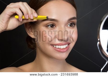 Portrait Of Delighted Attractive Girl Is Plucking Eyebrows With Smile. She Is Standing And Using Twe