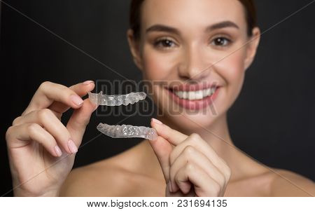 Taking Care Of Teeth. Close Up Of Clear Aligners In Hands Of Happy Girl Who Is Standing And Showing