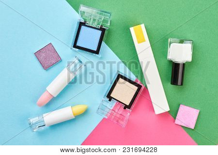 Makeup Cosmetics On Colorful Background. Lipsticks, Eyeshadows, Mascara, Nail Polish On Fashion Mult